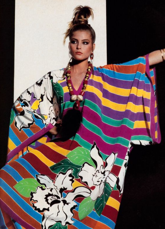 throwback thursday outfits, woman with blond top ponytail, wearing a wide-fitting dress with differently colored stripes and flower motives, over-sized ethno necklace, black and white background