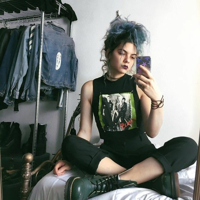 what did people wear in the 80s, young punk girl with died blue hair and dark lipstick, wearing black cropped pants and band t-shirt, with dark green army boots, sitting cross-legged on bed holding phone