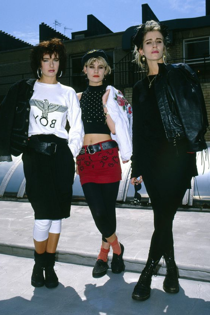 what did people wear in the 80s, three women with 80s style blond hair and clothes, black leggings white boy top, jeans and leather jackets, white cropped leggings and midi skirt, all black outfit