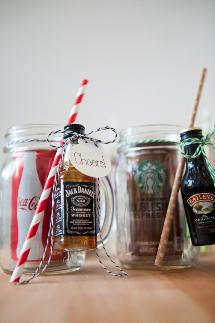 christmas crafts for adults, a can of coke in a clear jar with handle, a small bottle of whiskey and red and white straw tied to jar, a can of coke in clear jar with handle, brown spotted straw and small bottle of liqueur tied with green and white string