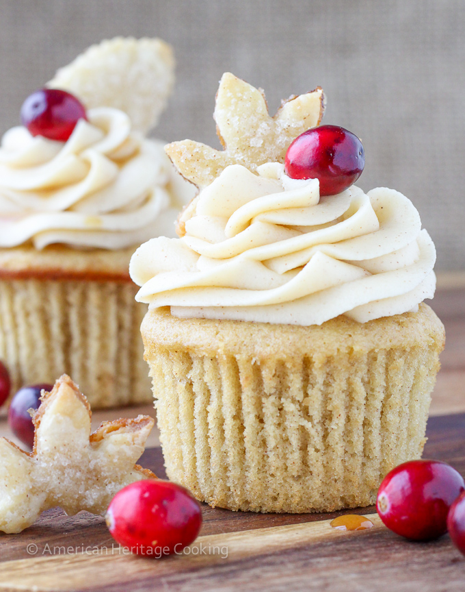 two pale brown cupcakes, with pale yellow icing, with leaf-shaped cookies and cranberries on top, on wooden table with more cranberries