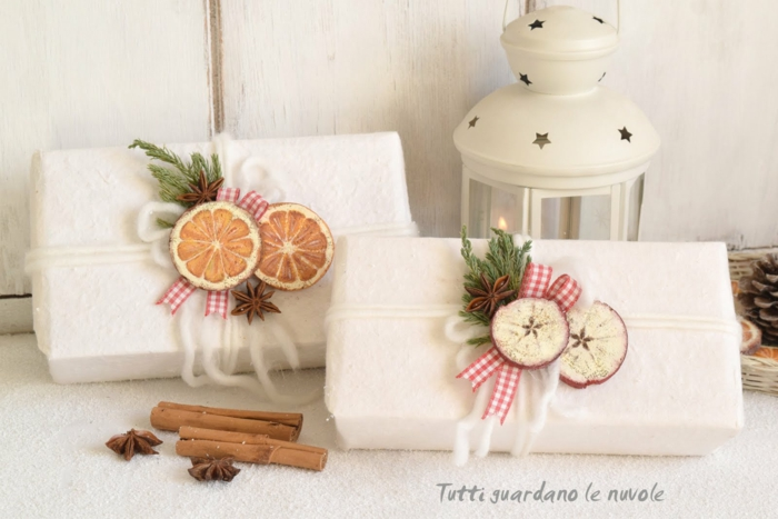 christmas crafts for adults, two gifts wrapped in fluffy white paper, tied with soft chunky white tread, decorated with painted wooden circles, green twigs and star anise, near cinnamon sticks and a white tin lantern