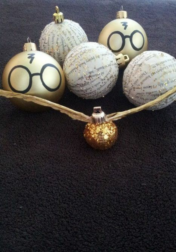 three christmas tree ornaments decorated with golden book pages and glitter and, two decorations with eyeglasses and a lightning scar drawn on them, one glittering golden ornament with wings