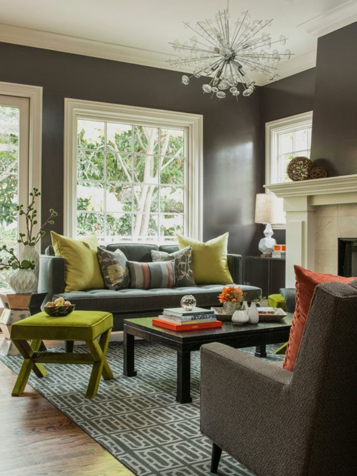two tone living room walls, dark brown walls with plaster details, white ceiling and glass chandelier, grey and white carpet, dark bluish-grey sofa with lime green and colorful cushions, lime green chair and wooden table
