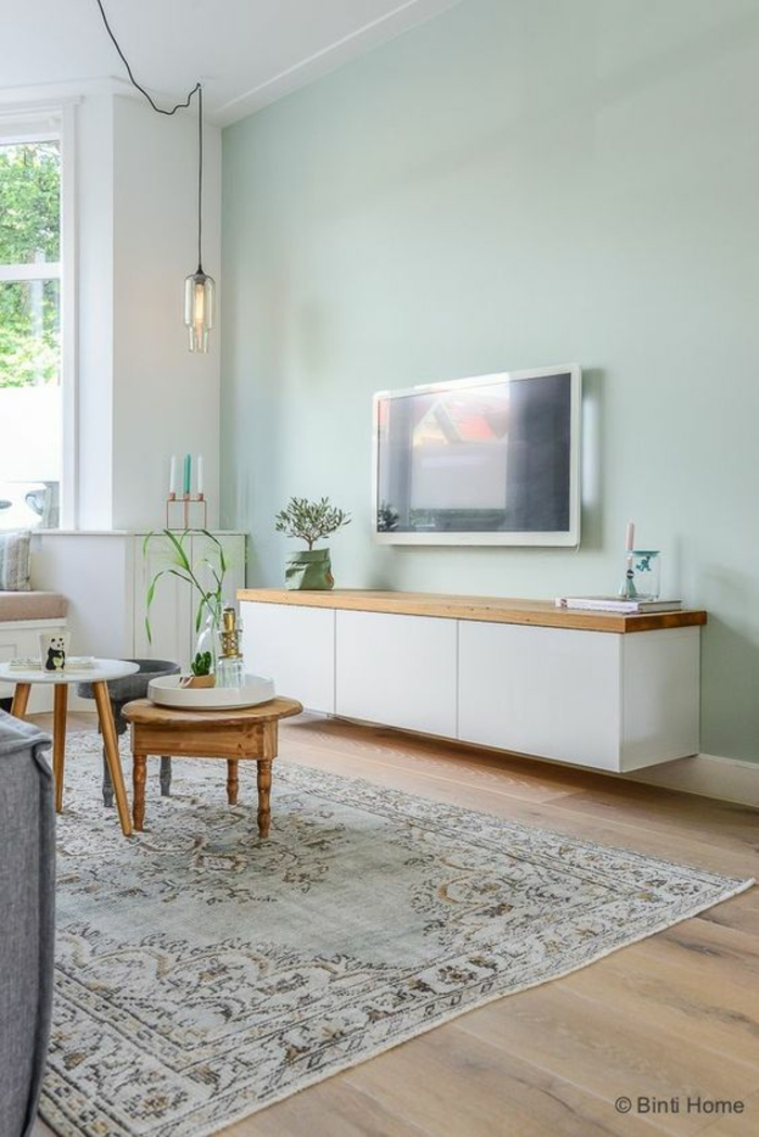 two tone living room walls, pale greenish-blue wall, opposing white wall with window, pale wooden floor and pale bluish carpet, two small coffee tables, white cupboard with wooden surface, lamp tv and plants