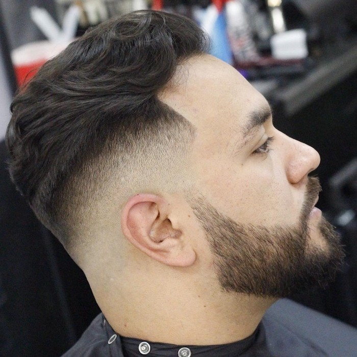 undercut fade, man in profile with hair long on top and shorter on the sides, with beard and mustache, wearing a black hairdresser's robe