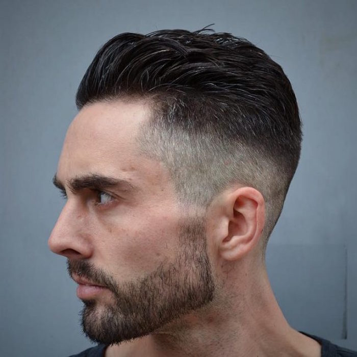 undercut fade, close up of man with black and grey hair, with mustache and beard, facing sideways and looking serious, with hair clipped short on sides and swept back on top