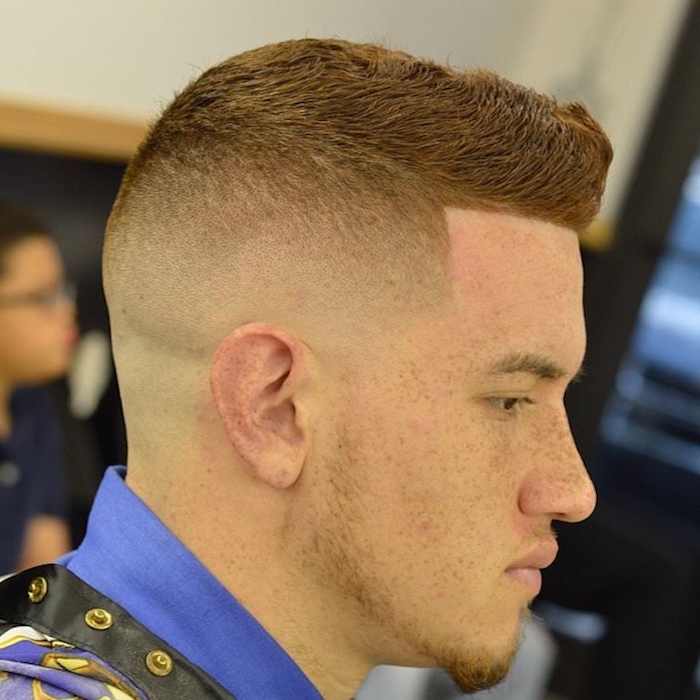 undercut fade, young ginger man with hair cut short on sides and kept long on top, with freckles and a small beard, wearing blue black and yellow barber's robe