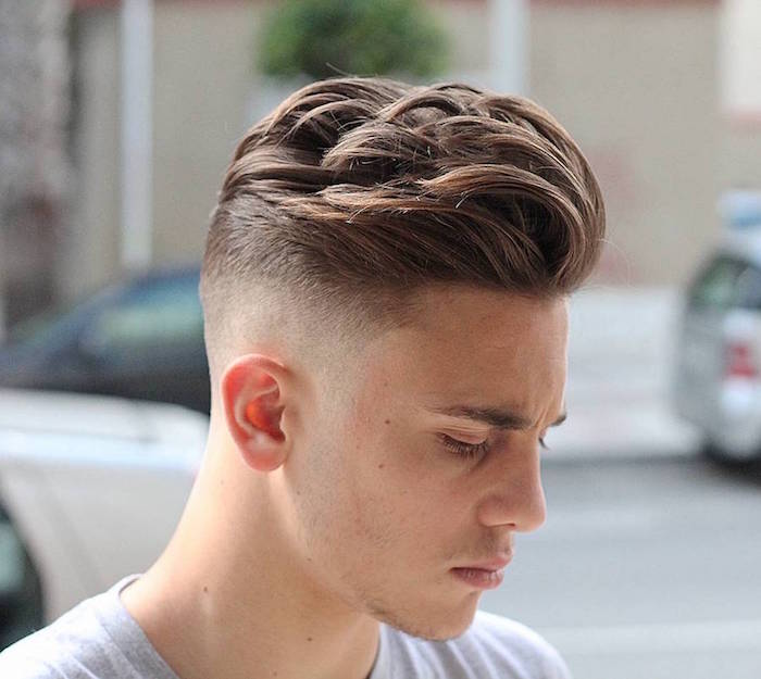 undercut fade, young man with chestnut hair, long and wavy on top and trimmed very short on the side, wearing light grey t-shirt facing sideways and looking serious