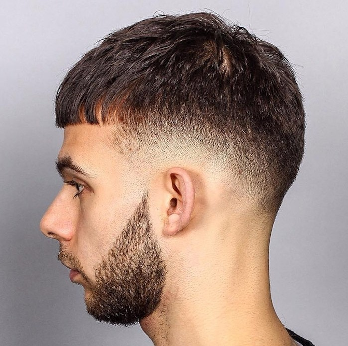undercut hairstyle men, pale man with trimmed beard and mustache, facing sideways in close up, hair on sides cut short, kept long on top with short bangs