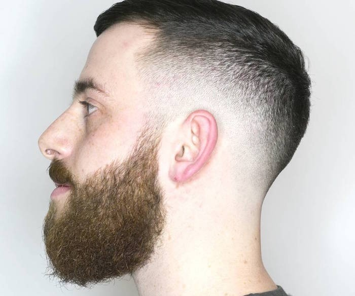 undercut hairstyle men, close up of a pale man in profile, beard and mustache, short hair on sides and slightly longer on top