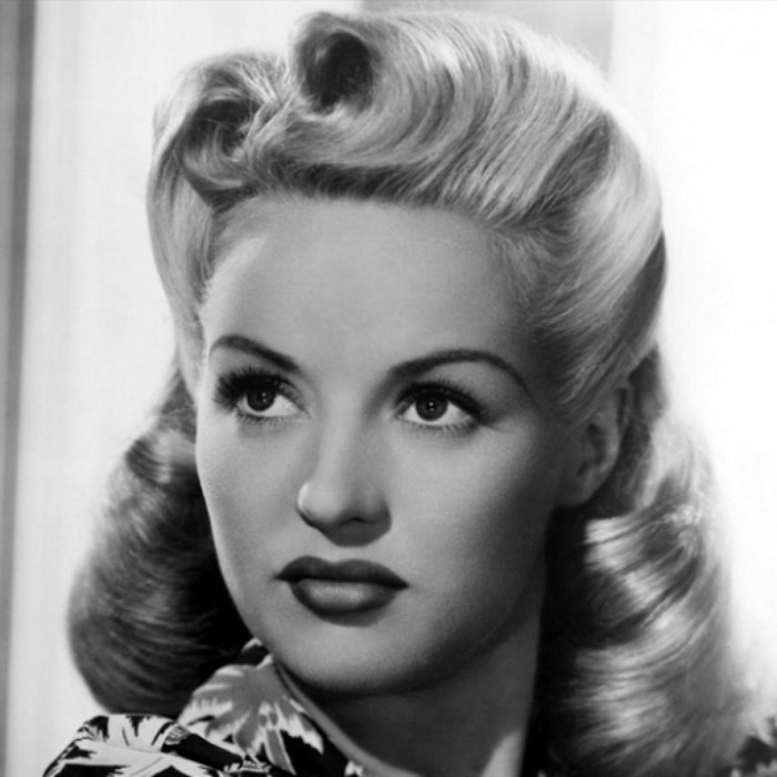 pinup hair, vintage black and white photo of woman with light hair and victory rolls, dark lipstick and big fake eyelashes, palm-tree printed top