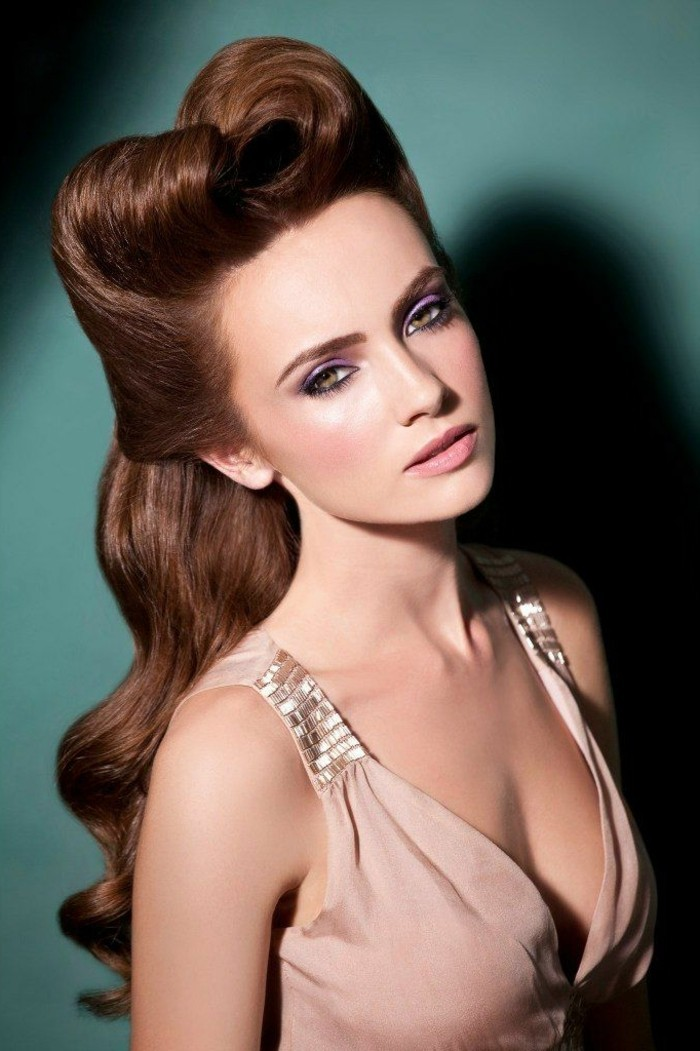 vintage hairstyles, long smooth brown hair with big lush curls and victory rolls, young woman with heavy eye make up, wearing a top in nude color