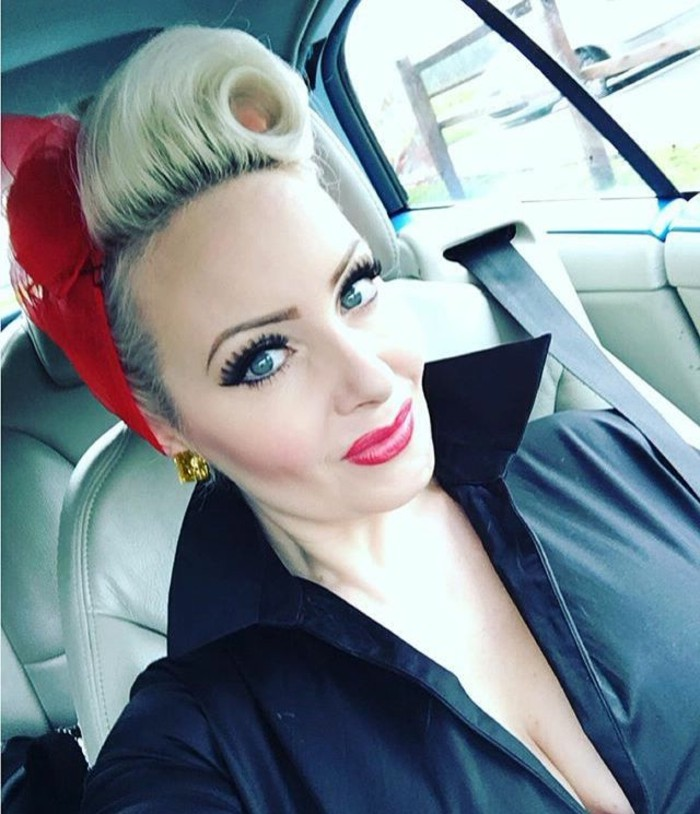close up of woman in car with heavy make up, fake lashes mascara and vibrant lipstick, dyed blonde hair with victory roll, red bandanna and black top