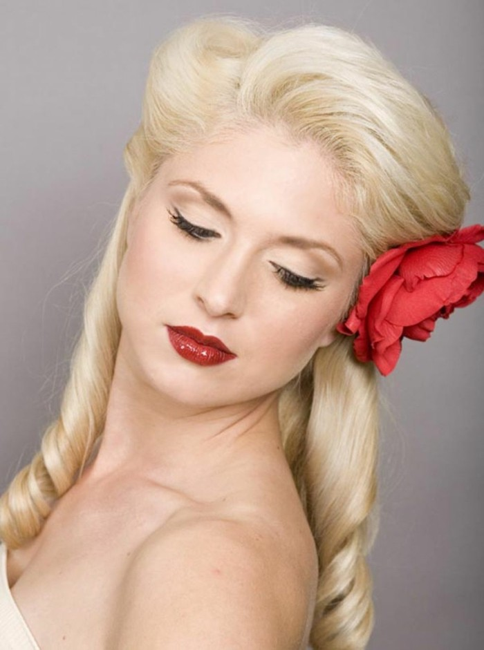 close up of a woman with dyed light blonde hair, retro curls and side swept bangs, with big fake rose and deep red shiny lipstick, fake eyelashes black eyeliner and mascara, bare shoulders