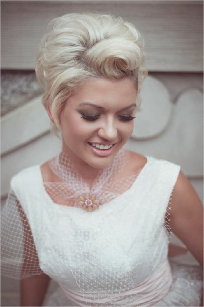 happy smiling woman with short platinum hair, styled with victory rolls, dark smoky eye make up, pale nude lipstick, white dress with white mesh details and flower broach