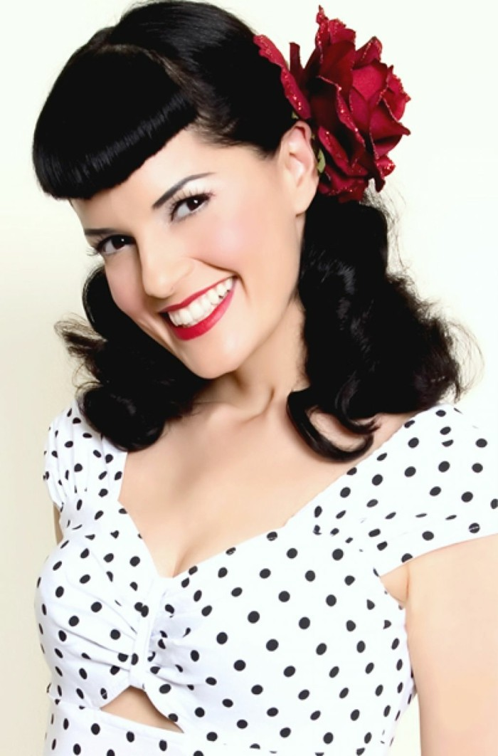 betty bangs, smiling woman with white teeth and bright red lipstick, shoulder-length wavy hair and a fake red rose ornament, white top with black polka dots