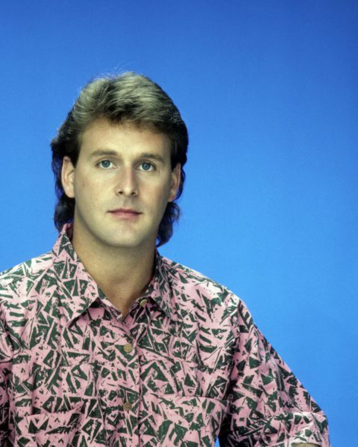 80's fashion for men, man with pale pink shirt, scribbles or geometric print, light brown mullet, plain blue background