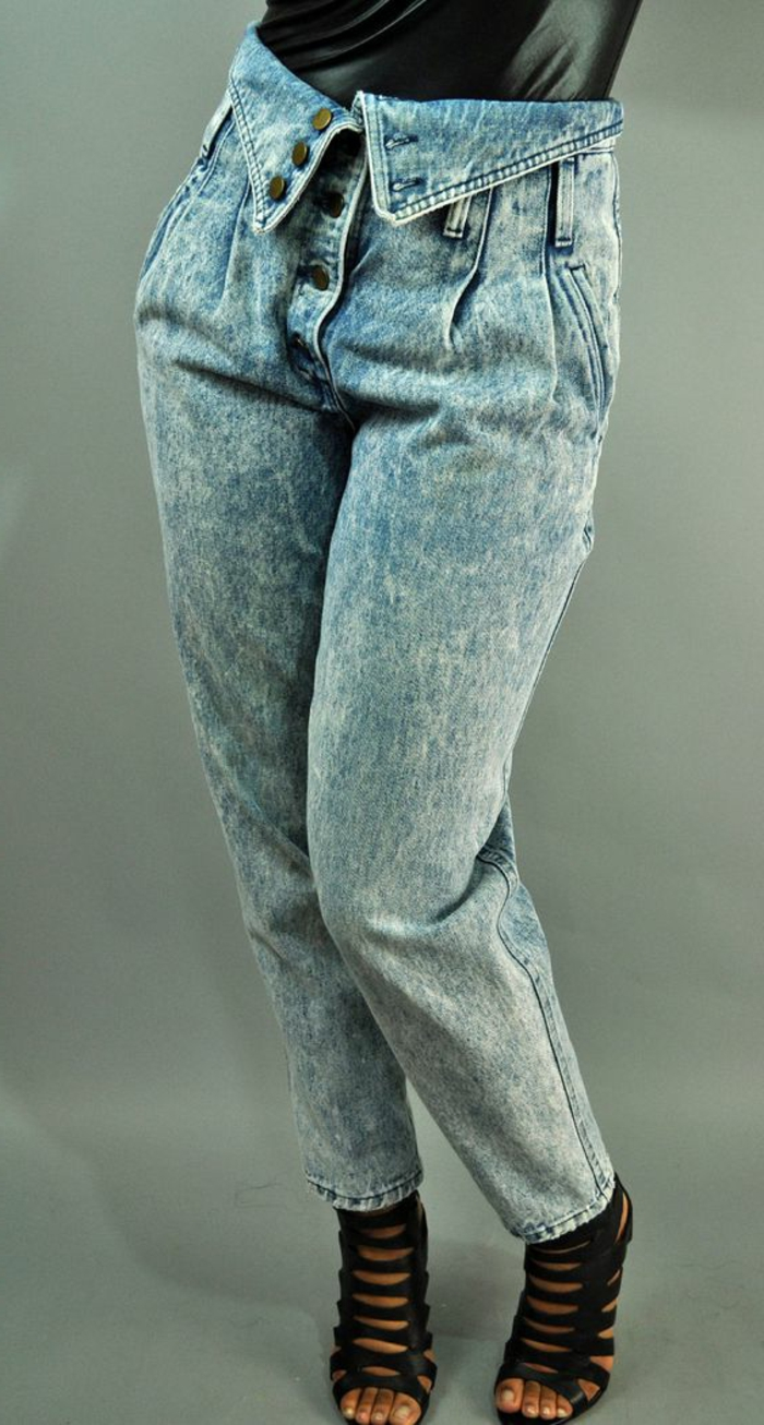close up of woman's lower half, wearing high-wasted acid wash jeans with button fold over detail, black sandals with many straps and black shiny top