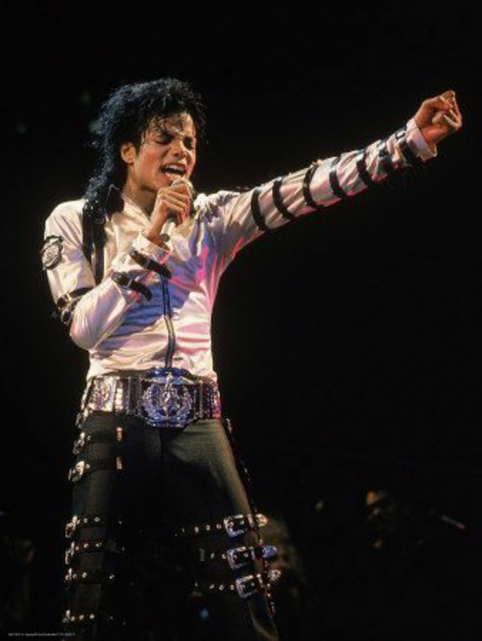 80s fashion trends, Michael Jackson holding microphone and singing, eyes closed one hand stretched out in fist, white shining zip-up shirt, black leather trousers