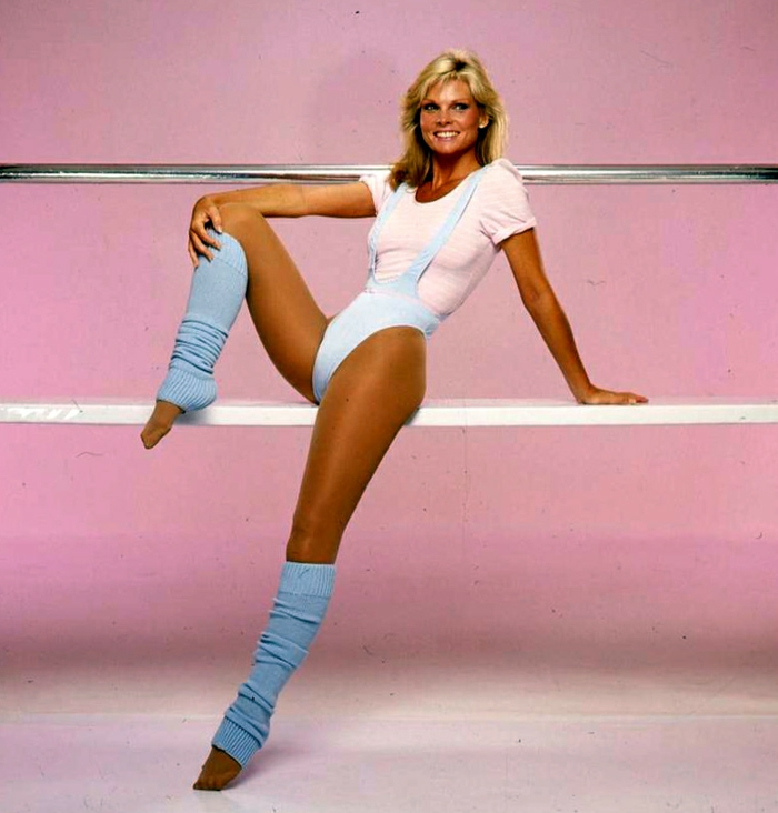 smiling blonde woman in 80s working out clothes, with pastel baby blue sports body suit and legwarmers and pastel baby pink t-shirt, leaning on white bar, pink background and metal bar
