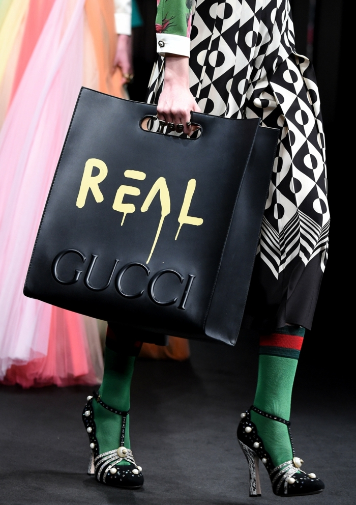 big black bag with inscription reading real gucci, held by woman in black and white dress with geometric pattern, green red and white sleeves, green and red socks and black and white shiny heels
