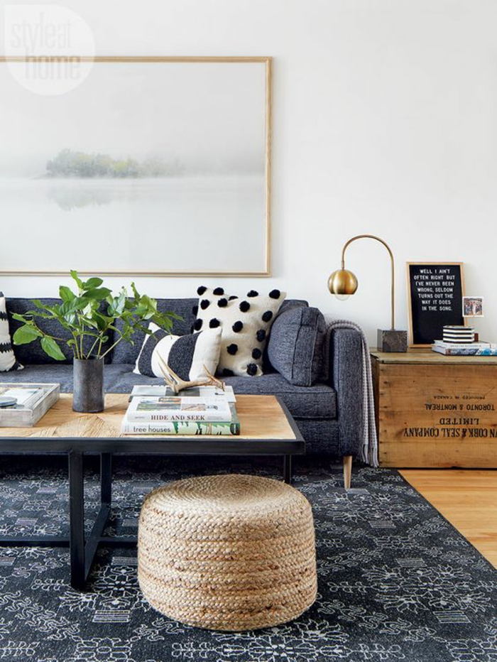 living room paint colors, dark blue sofa with white and navy pillows, wicker bean chair, light artwork in gold frame, dark blue carpet with white dteails