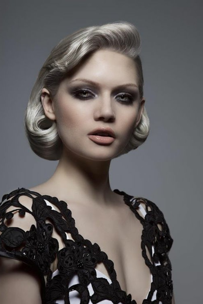platinum blonde woman with short hair in 1940's style, pale nude lipstick and heavy eye make up, with black eyeliner and mascara, black and white top and grey eyes