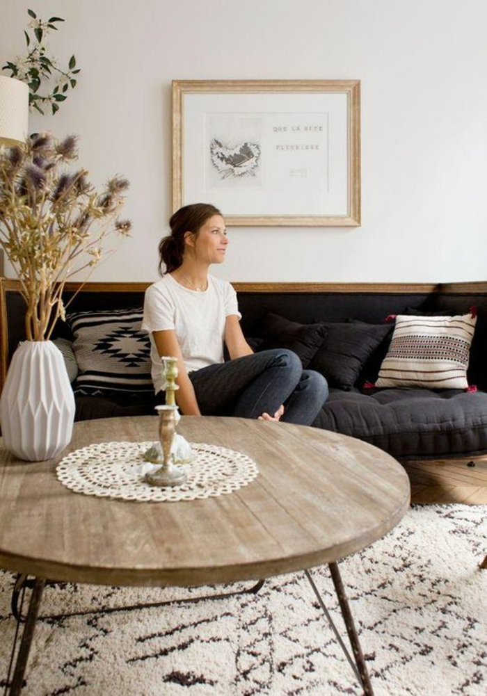 round wooden table with small crocheted cover, two candlesticks and a white vase with dry thistles, cream and dark brown carpet, woman sitting on dark blue sofa, white wall with framed image