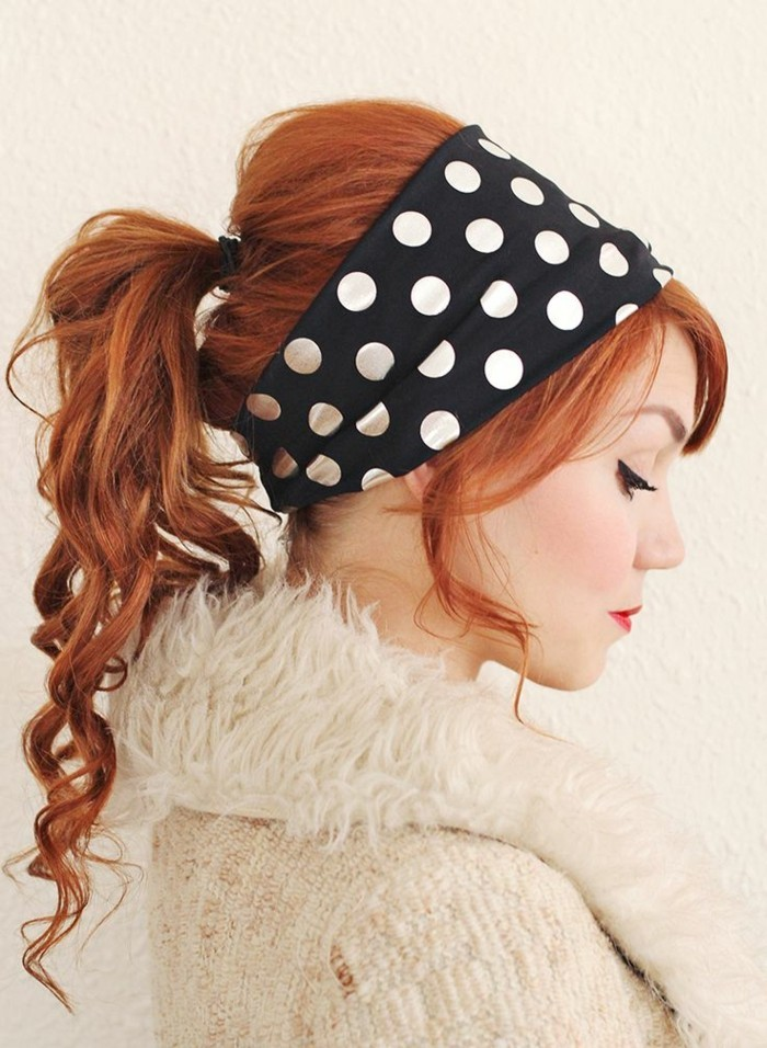 pin up hairstyles, copper red or ginger haired woman, hair tied in curly ponytail, eyeliner and red lipstick, wearing a fluffy cardigan and looking down