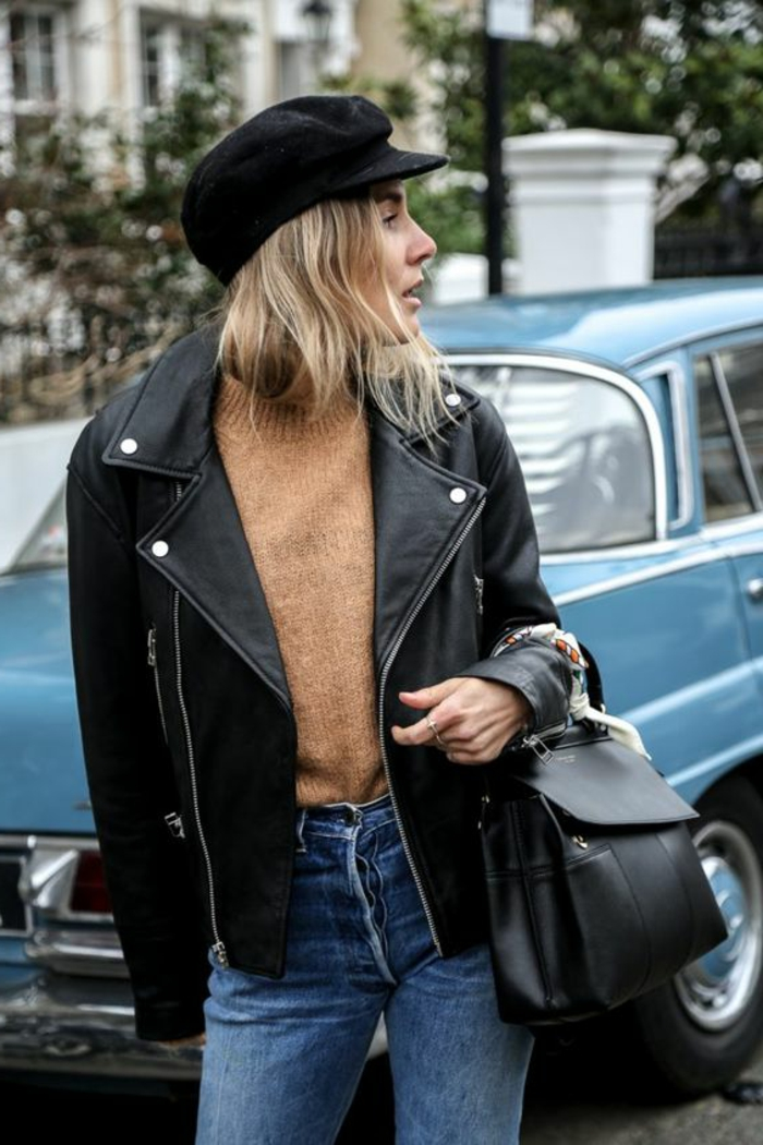 blonde woman with shoulder-length hair and black cap, wearing light brown sweater and acid wash blue jeans, with black leather biker jacket, holding a small black backpack
