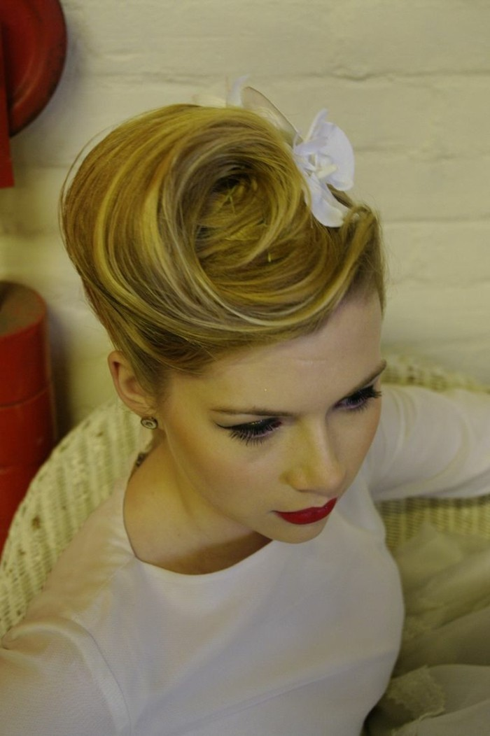 blonde woman with vintage swirly updo, and white hair ornament, wearing white top red lipstick and black eye make up, sitting on chair and seen from above