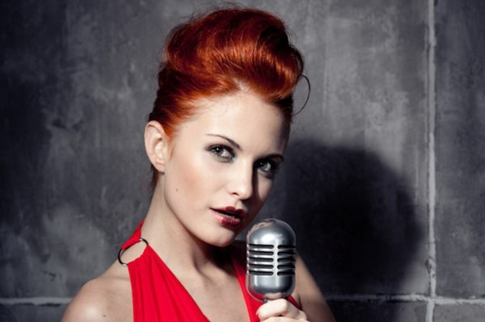 rockabilly hairstyles, red-haired woman with hair done up, dark red lipstick blush and eye makeup, red dress with metal detail, holding vintage microphone