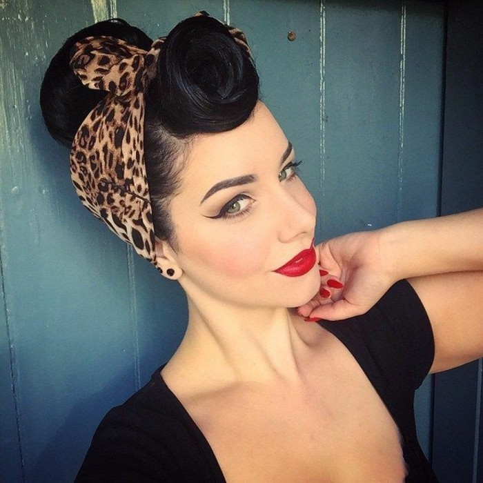 rockabilly hair, smiling woman with black hair, victory roll curled bangs and an animal print bandanna, heavy makeup featuring very bold eyeliner and bright red lipstick