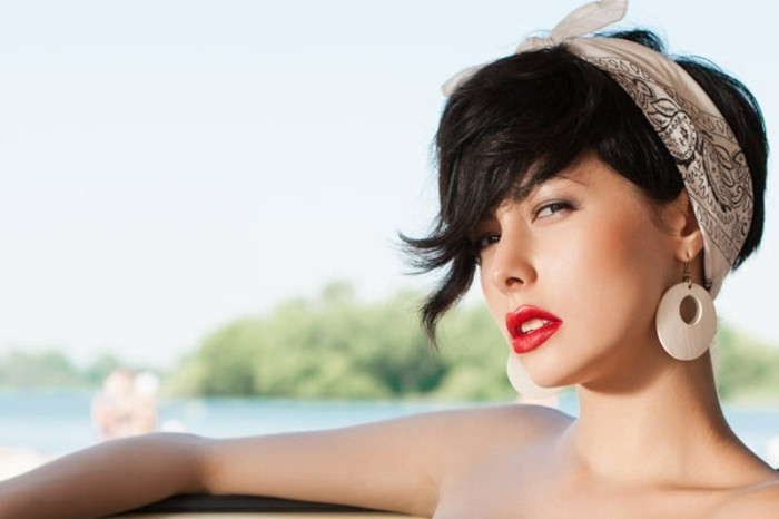 rockabilly hairstyles, serious-looking woman with long black bangs, hair tied with white and black bandanna, big white earrings and bright red lipstick, water and trees in background