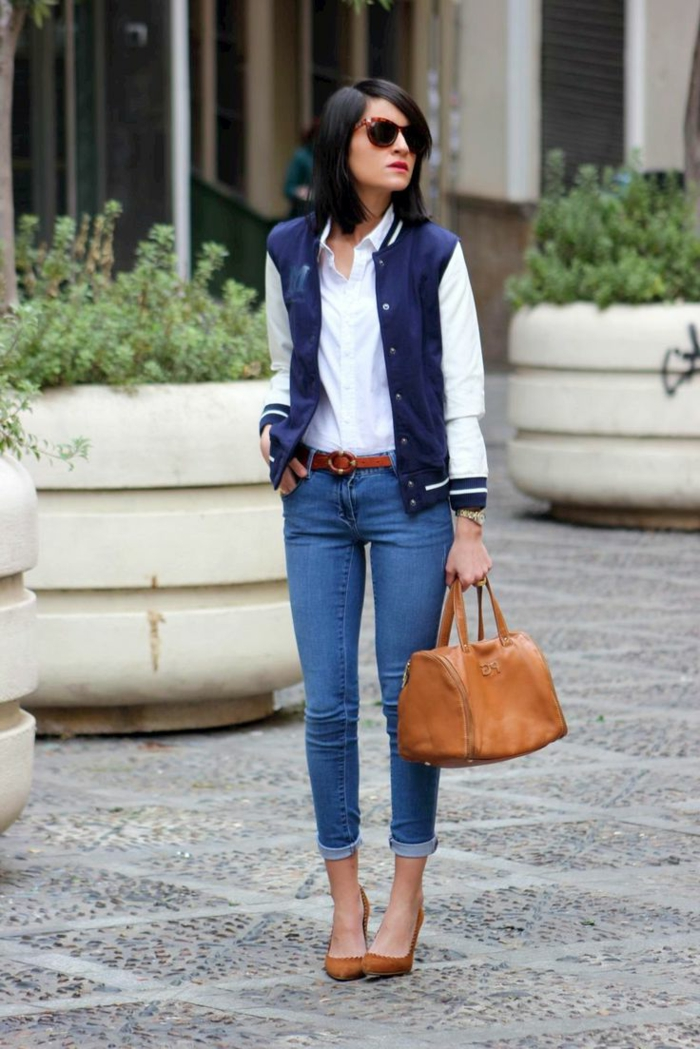 black-haired woman with sunglasses, wearing skinny ankle jeans, white formal shirt under blue and white baseball jacket, with brown high-heels and bowling bag