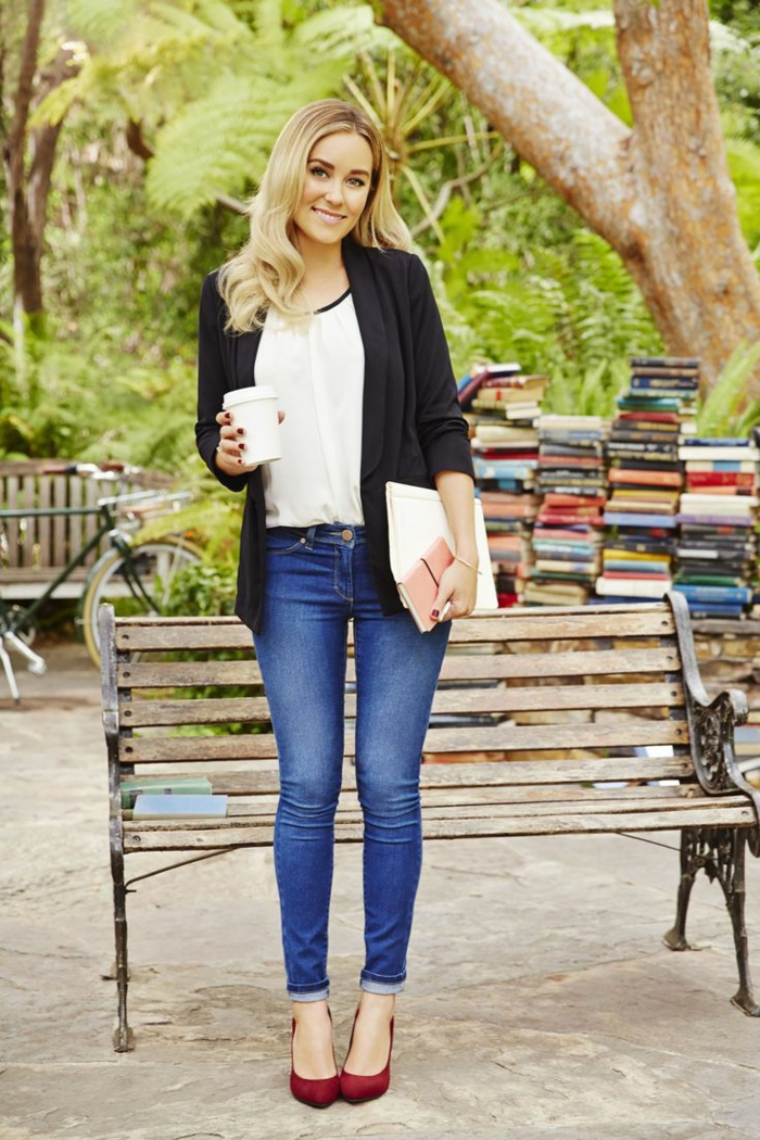 smiling blonde woman with wavy hair, wearing skinny jeans and a white top, dark purple high heels and black cardigan