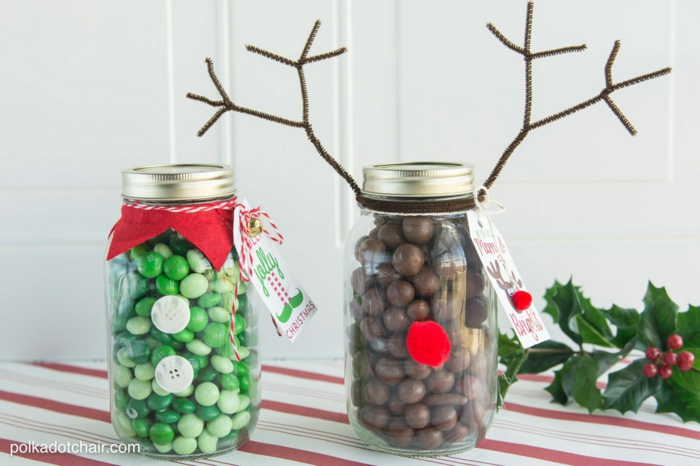 family christmas gifts, clear mason jar with screw-top lid, with 2 green buttons and a red collar containing green candy, jar with red pom-pom nose and wire antlers containing chocolate candy, a branch of holly