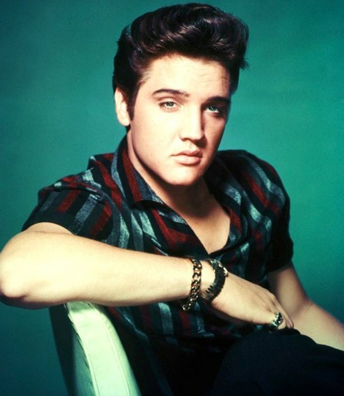 colorized photo of elvis presley leaning on white chair, dark gelled up hair, red grey and black striped short sleeved shirt, chain bracelet ring and wrist watch