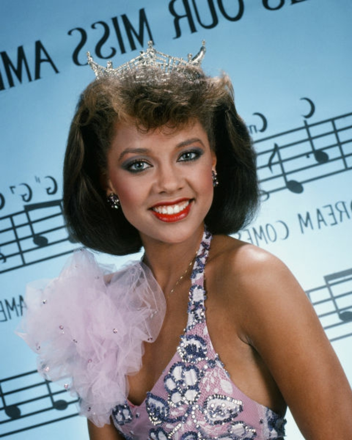young smiling African-american woman with red lipstick and blue eye shadow, wearing pink 80s embroidered top with mesh decoration, with jewelry and a golden tiara or prom queen crown