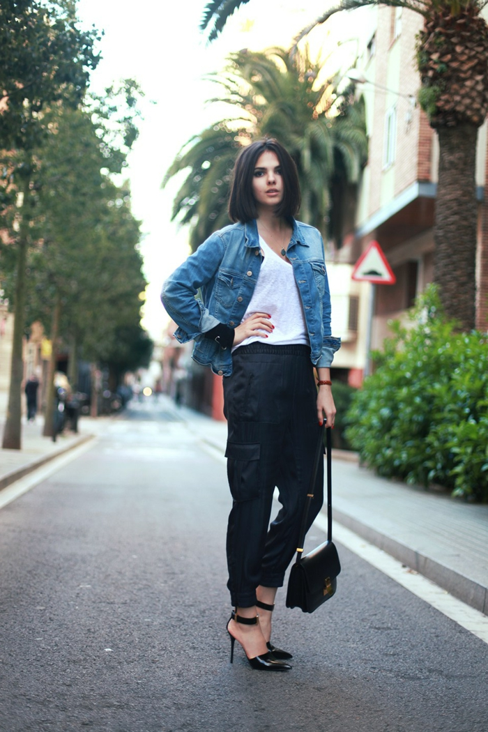 young woman with dark cropped hair, wearing denim jacket over white top, black cargo pants and strappy high heels, hand on hip and small black bag