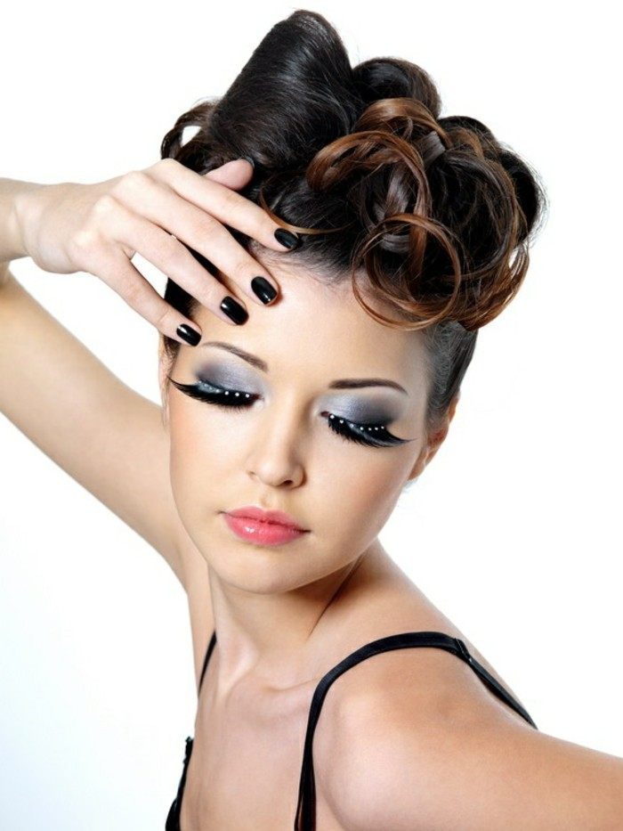 pinup style, woman with unusual curly updo, smokey eye make up, extremely long eyelashes with with drop decorations, pink shiny lipstick and black nail polish, closed eyes