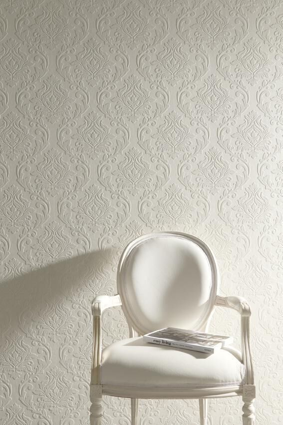 ornamental wallpaper in light cream, featuring Victorian-style symmetrical floral pattern, ornate white chair with magazine