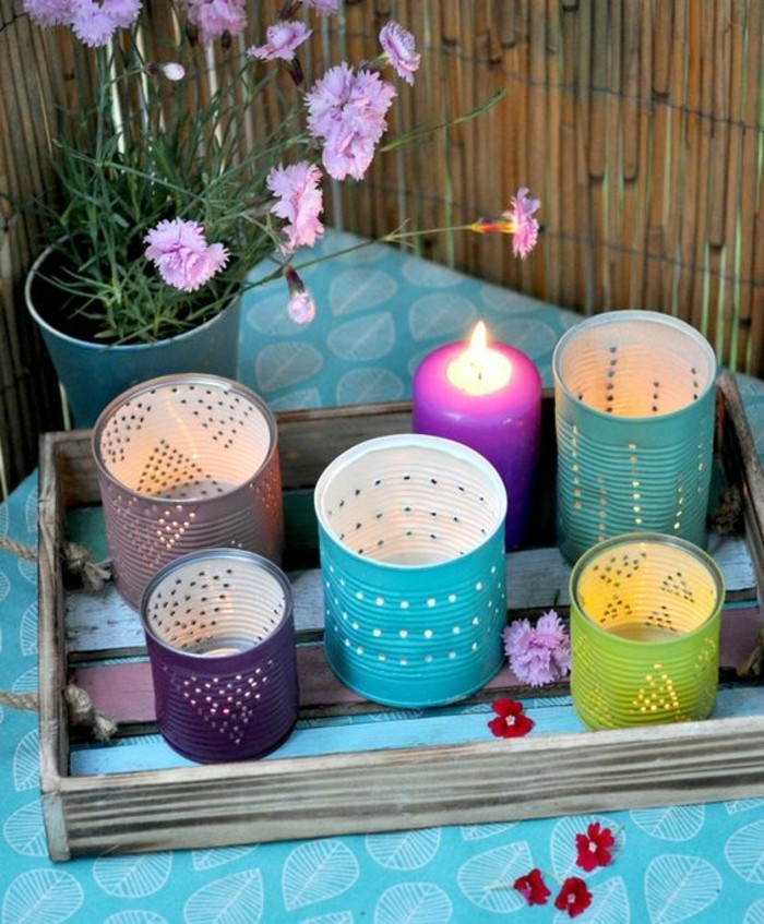five cans, painted in different colors, with small holes forming shapes, placed on a wooden tray, near a lit purple candle