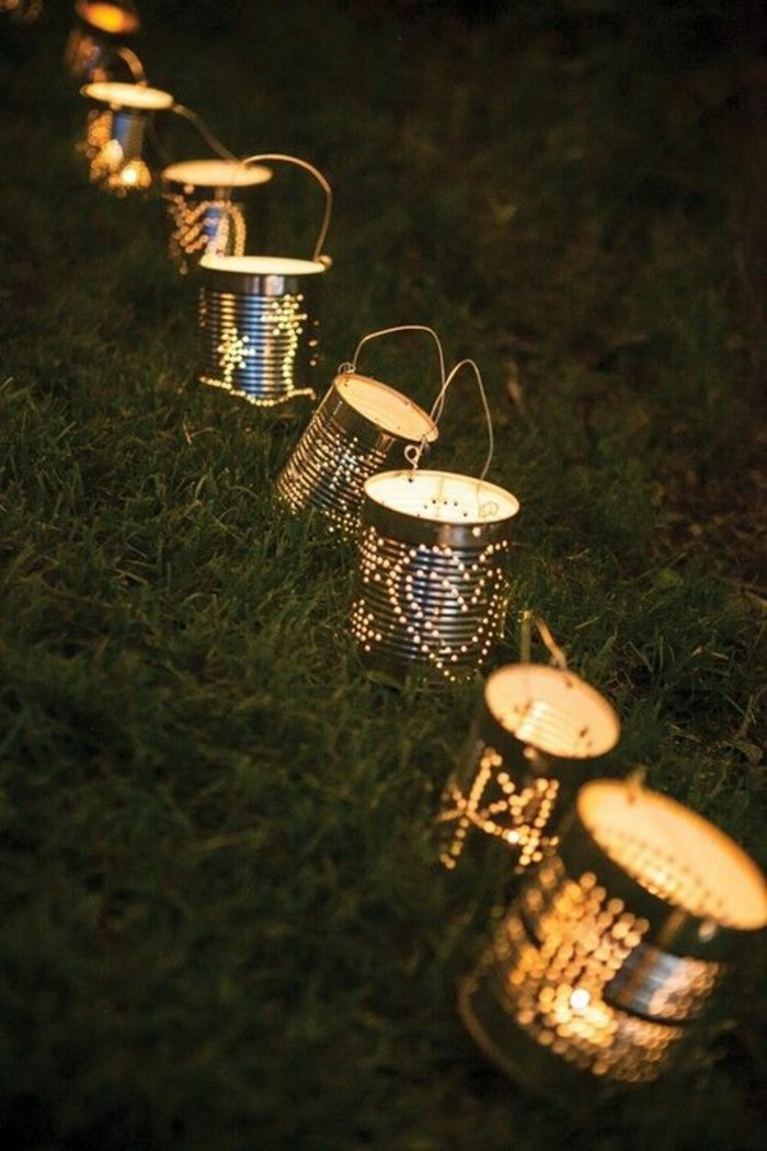 many luminaries made from plain tin cans with holes, with lit candles inside and with wire handles, placed on grassy area