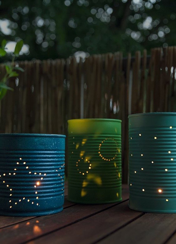 three luminaries made from cans in blue and green, with little holes forming different shapes, lit from within
