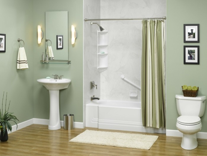 bathroom remodel, pale green walls, white ceramic sink and toilet, mirror and two wall lamps, white and grey open plan shower area with green curtain