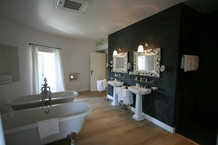 bathroom makeovers, light wooden floor, one wall decorated with dark wallpaper and two ornate mirrors, other walls painted white, two white ceramic tubs and sinks