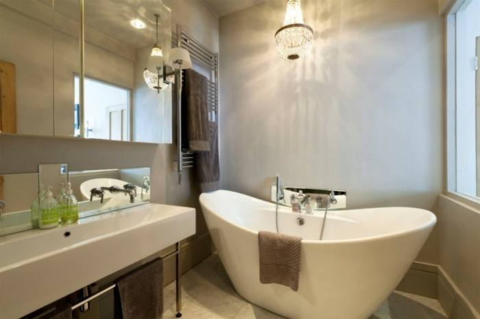 bathroom remodel, white ceramic tub, big white sink, mirrored cupboards and chandelier