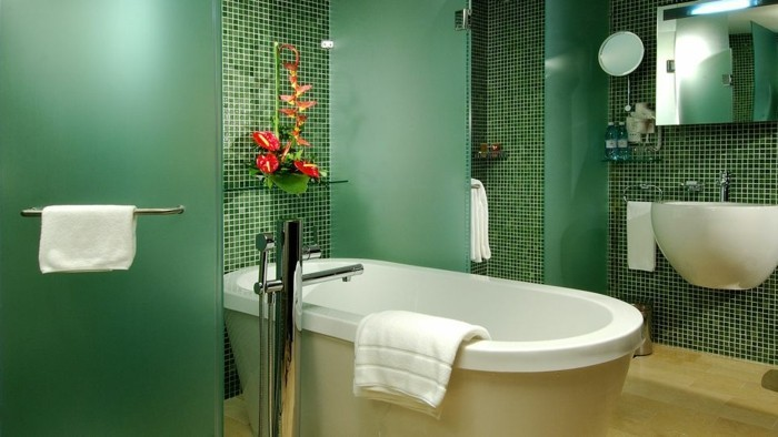 bathroom designs, walls with tiny green tiles in different shades, white ceramic tub and sink, shower cabin with green matte opaque glass